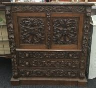A Victorian carved oak side cupboard
