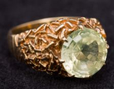A contemporary 9 ct gold ring, the pale green claw set stone above the bark effect shoulders.