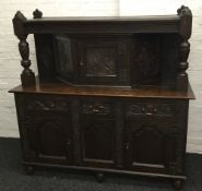 A late 19th/early 20th century carved oak court cupboard