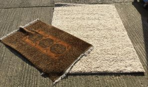 A large modern white ground rug and another