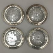 A set of four sterling silver and glass coasters
