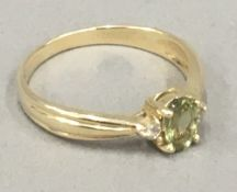 A 9 ct gold peridot and diamond ring (2 grammes total weight)