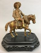 A 19th century gilt bronze group, modelled as a young man riding an horse side saddle,