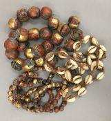 Two strings of Buddhist beads and an African cowrie shell necklace