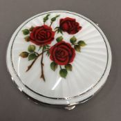 A vintage silver and enamelled compact decorated with red roses