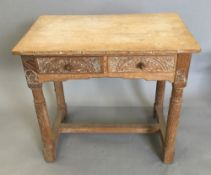 A carved limed oak side table with two drawers