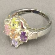 A silver and multi-coloured stone ring
