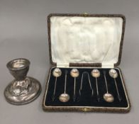 A cased set of silver coffee spoons and a silver candlestick