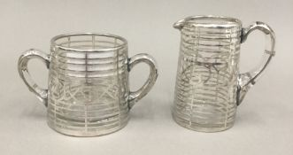 A glass and sterling silver overlay cream jug and sugar bowl