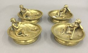 A set of four late 19th/early 20th century brass ashtrays each mounted with a bronze monkey smoking