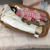 A basket of child's dolls, linen, etc.