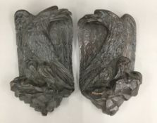 A pair of 19th century carved oak eagle wall plaques
