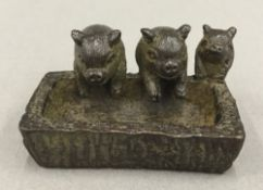 A small bronze model of pigs at a trough