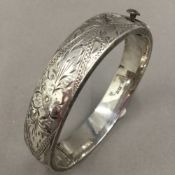 A silver bangle form bracelet