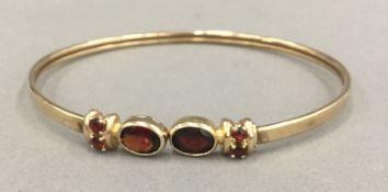 A 9 ct gold and almandine garnet bangle (8.