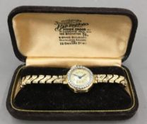 A 9 ct gold and diamond ladies watch, with plated strap (17.