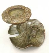 A bronze model of a frog sitting on a lily