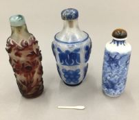Two Chinese cameo glass snuff bottles and another blue and white porcelain snuff bottle