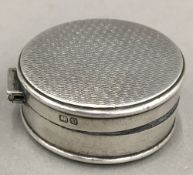 A small silver patch box