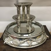 A vintage silver plated three-tier cake stand with stop-fluted corinthian capped column supports on