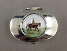 A silver pill box depicting a horse