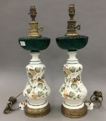 A pair of Continental decorated pottery table lamps with coloured glass reservoirs