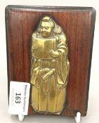A 19th century brass set wooden plaque depicting a figure,