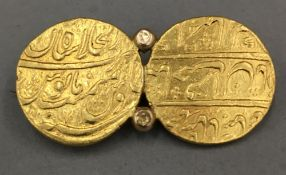 A brooch formed from two Middle Eastern, possibly Persian, unmarked gold (tests as 22 ct) coins (22.