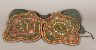 A Tibetan shoulder guard Mounted with various hardstone corals and shells. 65 cm wide.