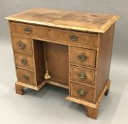 An 18th century style walnut kneehole desk The moulded crossbanded rectangular top above an