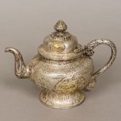 A Tibetan unmarked silver teapot With dragon form handle and gilt decorated in the round with gilt