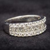 An 18 ct white gold three strand diamond ring Set with princess and brilliant cut diamonds.