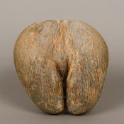 A coco de mer Of typical form, in natural unpolished state. 28 cm high.