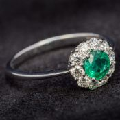 An 18 ct white gold diamond and emerald cluster ring Of flowerhead form. 8 mm high.