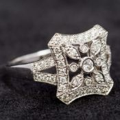 An 18 ct white gold diamond set ring Of pierced lobed square form with central floral design above