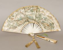 A 19th century Japanese fan The blade decorated with farm workers before a mountainous landscape,