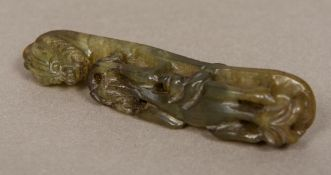 A Chinese carved jade belt hook Typically formed as a dragon. 11.75 cm long.