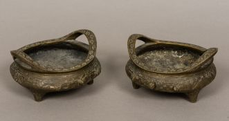 A pair of Chinese cast bronze censers Each of squat circular form with twin handles,