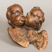 An 18th/19th century Continental stained softwood carving Worked as two winged putti masks.