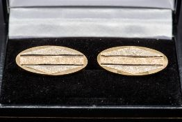 A pair of two-tone 18 ct gold cufflinks Each of oval form. Each approximately 2.75 cm wide.