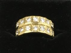 An 18 ct gold diamond ring Set with two rows of seven diamonds. 9mm high.