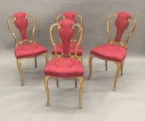 A set of four 19th century giltwood framed upholstered salon chairs Each shaped back with central