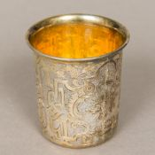 A Russian silver gilt tumbler cup Engraved in the round with scrolling decorations and a vacant