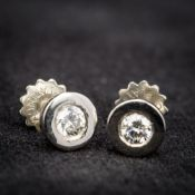 A pair of platinum and diamond stud earrings Each of plain circular form. Each 6 mm diameter.
