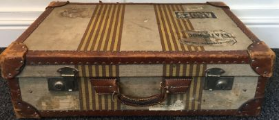 An early 20th century leather and canvas suitcase With banded decoration and applied travel labels.