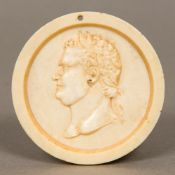 A 19th century carved ivory roundel Of dished form, centred with a male bust,