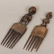 Two African carved and stained wood combs Each figurally mounted.