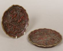 A pair of Chinese cinnabar lacquer on bronze plates Each deeply worked with various figures in