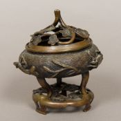 A Chinese patinated bronze censer The pierced florally decorated cover above the main body cast