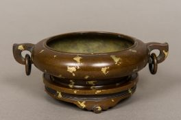 A Chinese gold splash patinated bronze censer Of squat circular form with twin loop and ring